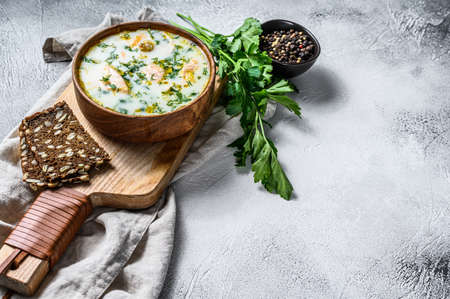 Creamy fish soup with salmon, trout, potatoes and parsley. Gray background, top view, space for text.