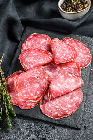 Spanish salami salchichon on a black chopping Board. Black background. Top view.