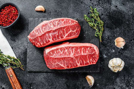 Raw organic meat Twagyu oyster top blade steak. Black background. Top view. Banco de Imagens