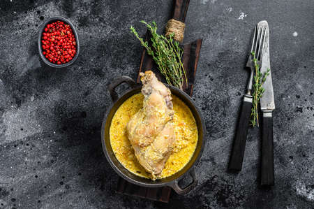 Roasted Rabbit Haunches in Pan with Stewed Vegetables. Black background. Top view.