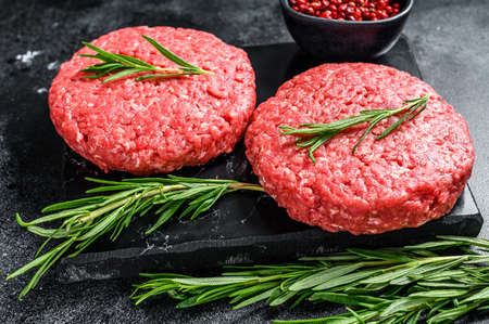 Patty of minced meat for burger. Black background. Top view. Imagens