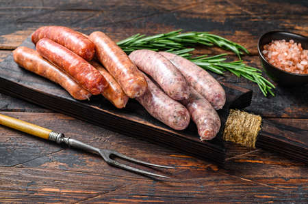 Raw homemade sausages on a cutting board. Dark wooden background. Top view.