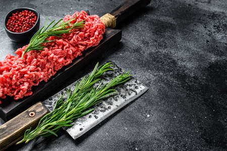 Fresh Raw mince beef, ground meat with herbs and spices. Black background. Top view. Copy space.