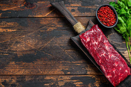 Raw skirt or machete beef meat steak on a cutting board. Dark wooden background. Top view. Copy space.