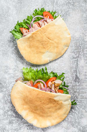 Doner kebab with grilled chicken meat and vegetables in pita bread. Gray background. Top view. Stock Photo