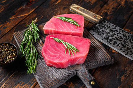 Raw tuna steaks on a wooden cutting Board with cleaver. Dark wooden background. Top view.