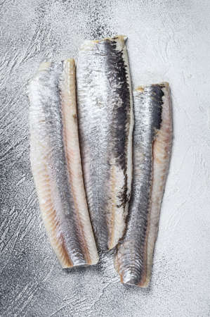 Pickled marinated sea herring fillet. White background. Top view