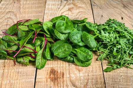 Mix Salad leafs, Arugula, Spinach and swiis Chard. Wooden background. Top view