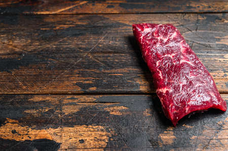 Raw machete or skirt beef steak. Dark wooden background. Top view. Copy space