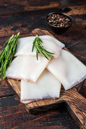 Raw Calamari or Squid on a wooden board with rosemary. Dark wooden background. Top view Stock fotó