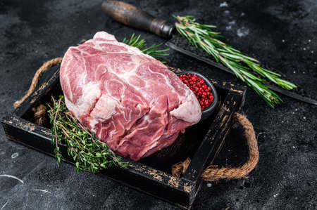 Raw pork neck meat piece for Chop steak in wooden tray with herbs. Black background. Top view