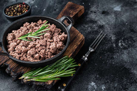 Fried mince beef meat in a pan for cooking pasta. Black background. Top view. Copy space