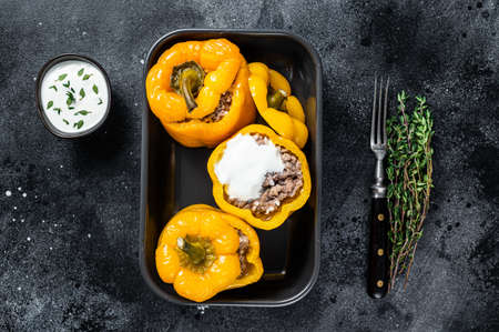 Baked yellow Sweet bell pepper stuffed with beef meat, rice and vegetables. Black background. Top view