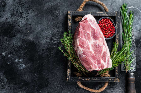 Raw pork neck meat piece for Chop steak in wooden tray with herbs. Black background. Top view. Copy space