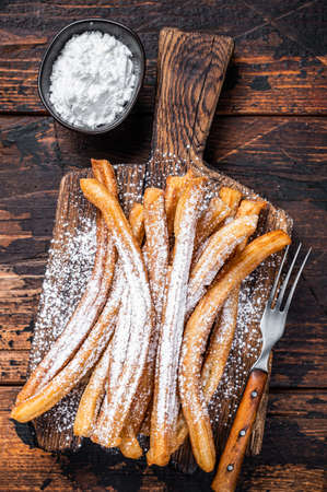 Spanish dessert churros with sugar powder on a wooden tray. Dark wooden background. Top view
