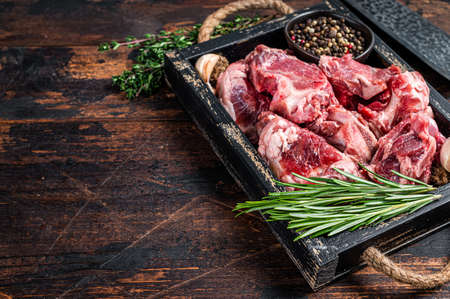 Raw lamb or goat meat diced for stew with bone. Dark wooden background. Top view. Copy space