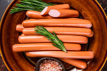 Wiener raw sausages in a rustic plate with herbs. Dark background. Top view Stock fotó