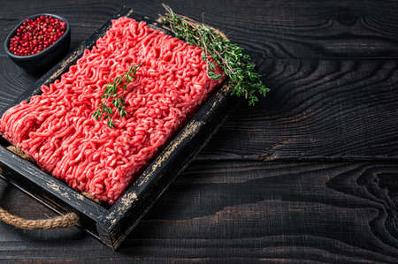 Raw mince ground beef and pork meat in a wooden tray with herbs. Black background. Top view. Copy space