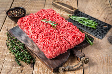 Fresh Raw mince beef meat on a butcher cutting board with cleaver. Wooden background. Top view Stock fotó