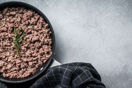 Fried ground mince beef and pork meat in a pan with herbs. White background. Top view. Copy space