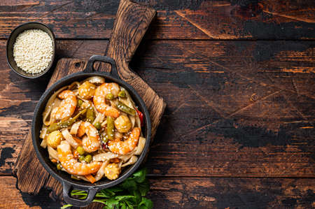 Asian Udon stir-fry noodles with shrimps prawns in a pan. Dark wooden background. Top view. Copy space