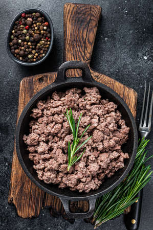 Fried mince beef meat in a pan for cooking pasta. Black background. Top view