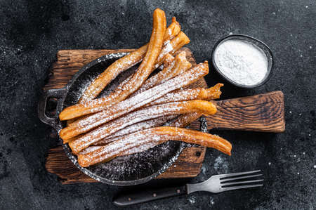 Traditional Mexican dessert churros with sugar powder in a pan. Black background. Top view