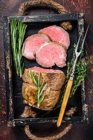 Roast beef round fillet meat in a wooden tray with herbs. Dark background. Top view