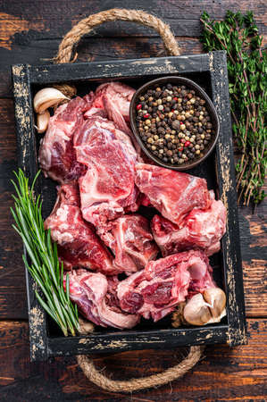 Raw lamb or goat meat diced for stew with bone. Dark wooden background. Top view
