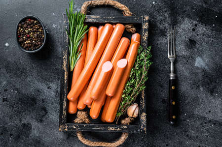 Frankfurter sausages in a wooden tray with herbs. Black background. Top view