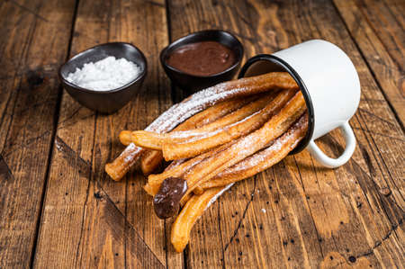 Churros with sugar and chocolate sauce. wooden background. Top view