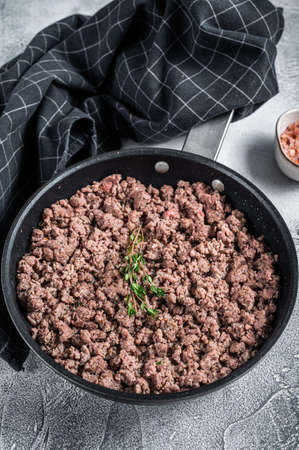Fried mince beef and lamb meat in a pan with herbs. White background. Top view