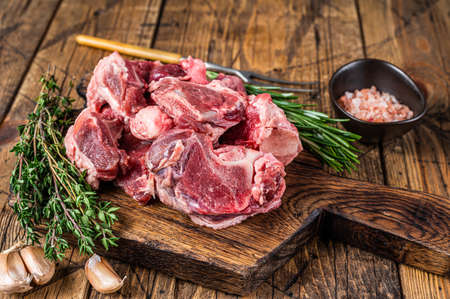 Raw beef meat diced for stew with bone. wooden background. Top view
