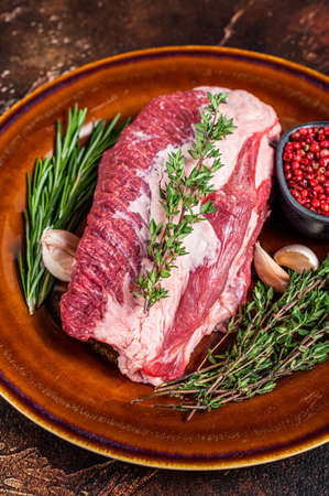 Raw round beef meat prime cut for roast on a rustic plate with herbs. Dark background. Top view