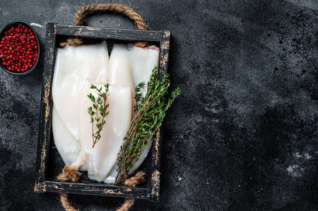 Raw white Squid or Calamari in a wooden tray with herbs. Black background. Top view. Copy space