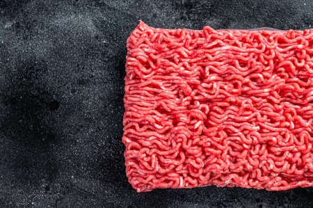 Raw mince beef meat on a kitchen table. Black background. Top view