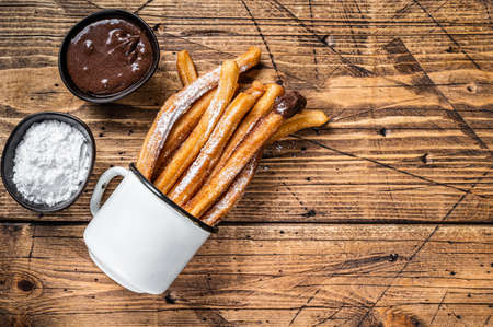 Churros with sugar and chocolate sauce. wooden background. Top view. Copy space