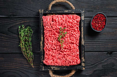 Raw mince ground beef and pork meat in a wooden tray with herbs. Black background. Top view Stock fotó