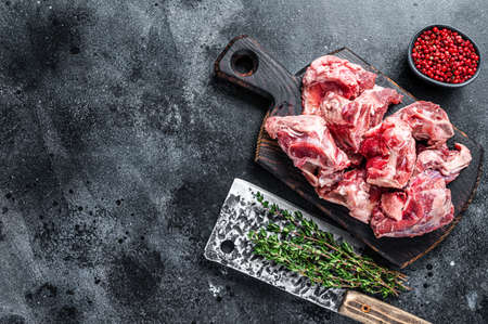 Raw lamb meat stew cuts with bone on wooden butcher board and cleaver. Black background. Top view. Copy space Stock fotó