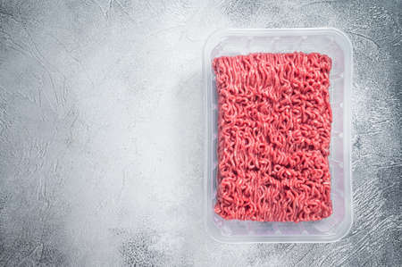 Raw ground beef and pork meat in vacuum packaging from super market. White background. Top view. Copy space