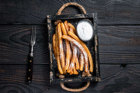 Churros fried sticks with sugar powder in wooden tray. Black background. Top view