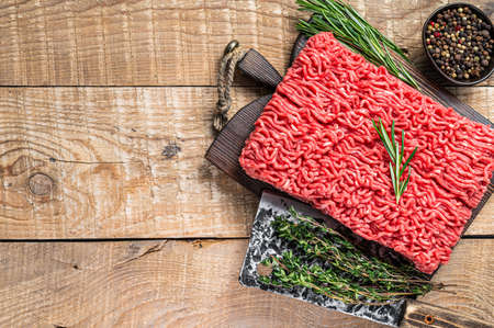 Fresh Raw mince beef meat on a butcher cutting board with cleaver. Wooden background. Top view. Copy space