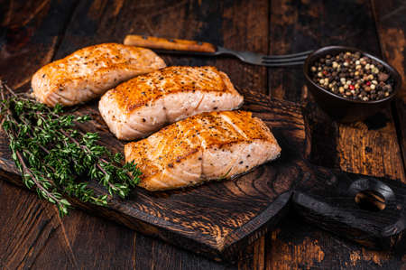 Fried Salmon Fillet Steaks on a wooden board with thyme. Dark wooden background. Top view Archivio Fotografico