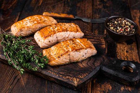 Fried Salmon Fillet Steaks on a wooden board with thyme. Dark wooden background. Top view Reklamní fotografie