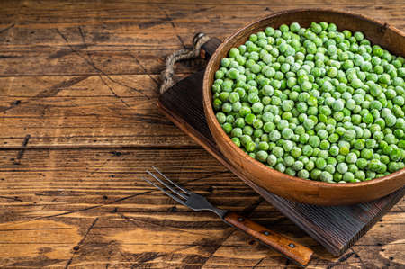 Cold Frozen green peas in a wooden plate. Wooden background. Top view. Copy space