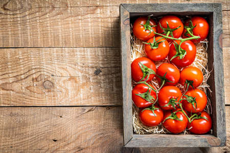 Red tomatoes in wooden market box. Wooden background. Top view. Copy space