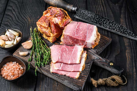 Smoked Sliced Pork loin Meat on a wooden cutting board. Black wooden background. Top view Stock Photo
