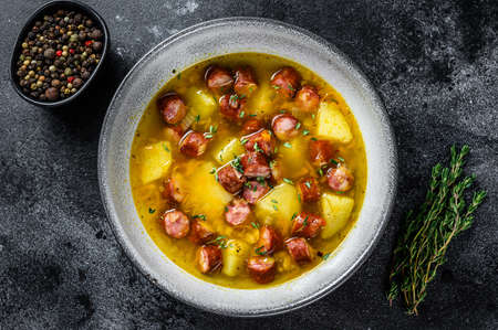 German Split pea soup with smoked sausages and meat. Black background. Top view. Copy space