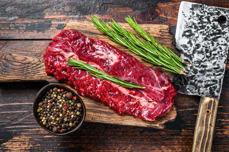 Butchers choice raw steak Onglet Hanging Tender beef meat on a cutting board. Dark wooden background. Top view