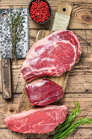 Fresh raw prime black angus beef steaks fillet Mignon, rib eye or cowboy, Striploin. Wooden background. Top view